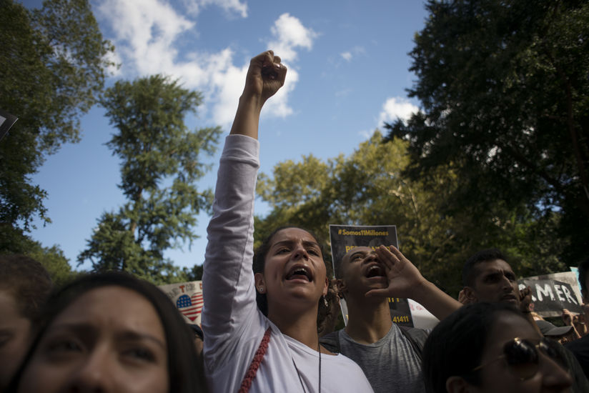 A protestor holds her fists in the air as she yells. A man who stands behind her and has his hand to his mouth and yells.