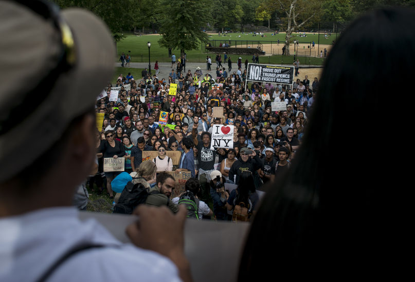 """Two people are blurred in the foreground. They are overlooking a crowd of protestors. In the middle of the crowd, a Black man in the crowd holds his fist in the air and a sign that says """"I love immigrant NY."""""""