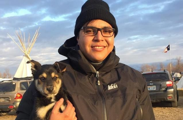 Chicano/Native artist in a black skull cap and jacket poses at a Standing Rock camp holding a puppy