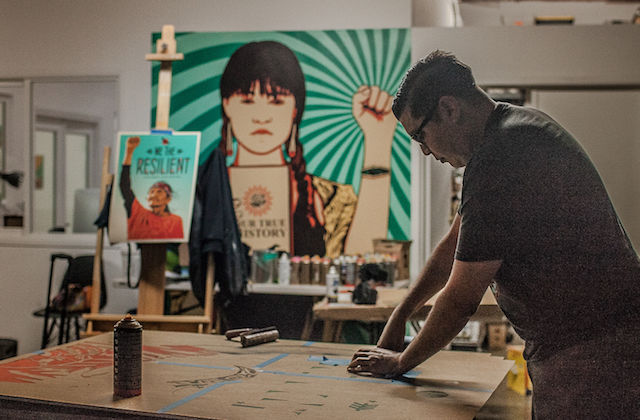 A young man wearing a t-shirt and jeans works at a drafting table with colorful posters of Native people in the background