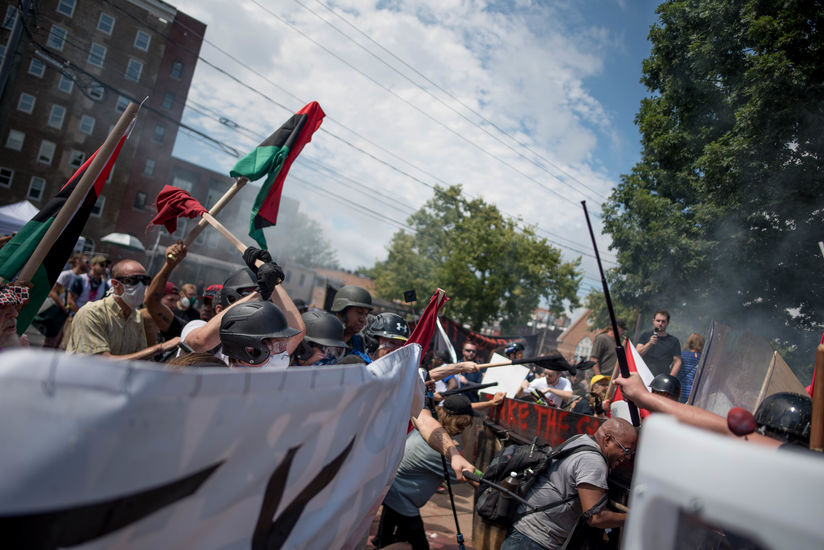 People holding red, black and green flags face off with helmeted White nationalists holding racist flags at the Unite the Right rally