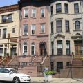 Bedford-Stuyvesant rowhomes in multiple colors with White car parked in front
