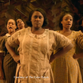 Black woman in faded cotton dress stands in front of five other Black women in cotton dresses