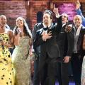 """Hamilton"" cast on stage in line with red brick background"