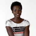 """Black woman with short, natural hair, wears white t-shirt that says """"I Am An Immigrant"""""""