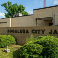 "Brown buildings reading ""Bogalusa Police Department"" and ""Bogalusa City Jail"" on green grass, blue sky in background"