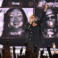 Queen Latifah in black outfit with hand raised, black-and-white images in background