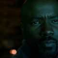 Mike Colter in navy hoodie with Black background