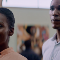 Tika Sumpter in peach-colored dress with Parker Sawyers in light blue shirt, both against blurry background