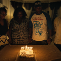 Six Black people surround a cake with lit candles