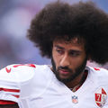 Colin Kaepernick with black afro and white jersey with red lettering against blurred blue-green background