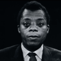 Greyscale footage of Black man in black suit with white shirt and black tie against black background