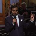 Brown man in navy suit with white shirt and red tie against brown background with black-clad musicians