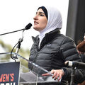 Woman in headscarf speaks behind podium