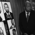 Black and white photo of Black man in suit and tie, seated next to posterboard of him as a young man in arrest photos