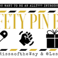 Gold, black and white logo featuring images of a safety pin, gift box and a fist