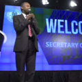 "A Black man in a suit and red tie stands before a blue backdrop with the words ""Welcome Secretary Carson!"""