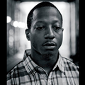 Greyscale image of Black man in plaid shirt against blurry background