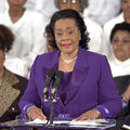Woman in purple suit speaks at podium.