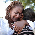 People hug following a jazz funeral ceremony at Dillard University on August 28, 2015, for the 10th anniversary in New Orleans, Louisiana.