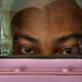 Black person's eyes are visible through a small window in a lavender door