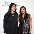 Brown woman in black dress next to Brown woman in half-black and half-multicolored dress in front of white wall with grey text