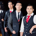 Four Asian men in black, grey, red and white formal wear against silver railing and black background with yellow lights