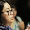 A young Latinx woman wearing glasses addresses a crowd