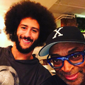 Black man with afro in black shirt standing next to Black man in black hat with white letter and black glasses in front of beige wall