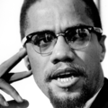 Black-and-white image of Black man in suit and glasses in front of grey background