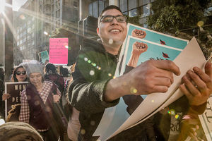 A smiling Chicano/Native man passes out colorful protest posters on a sunny day in L.A.