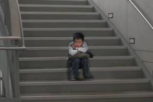 Boy on school stairwell with striped shirt