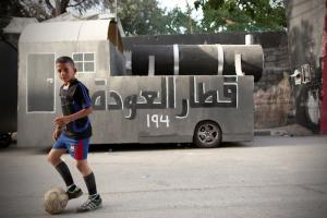 A young Palestinian boy in a black athletic T- shirt and blue shorts with a soccer ball at his feet