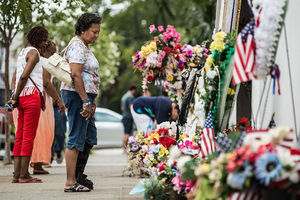 People stand looking at colorful memorial in front of white church