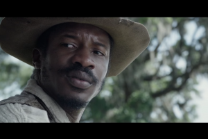 Nate Parker in beige hat and gray shirt and brown vest with tress in background