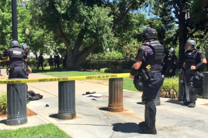 Police in black riot gear by yellow and black crime scene tape, with a pool of red blood on the ground