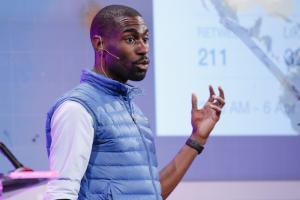 DeRay Mckesson in blue vest and white shirt, wearing handless microphone in front of blurry, multi-colored background