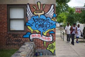 A blue, black, white, red and yellow mural is painted on a brick wall; it features Freddie Gray's name, date of birth and date of death