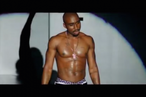 Black man wearing boxers and gold chains stands in spotlight on a dark stage