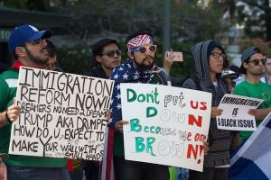 A line of protestors hold up signs calling for immigration reform