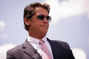 Milo Yiannopoulos in a dark grey pinstriped suit with white shirt and pink patterned tie