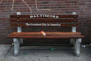 """A brown bench with the following message written on it: """"Baltimore: The Greatest City in America"""""""