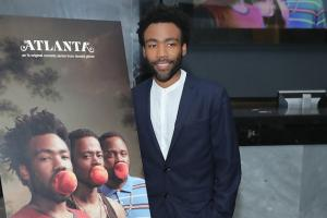 Donald Glover in navy suit with white shirt next to sign on black easel