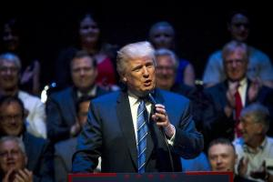 Trump in navy suit at brown podium, blurry images of faces behind him