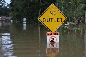 A sign is seen along a flooded road on August 15, 2016, in Baton Rouge, Louisiana. Record-breaking rains pelted Louisiana the weekend of August 12 leaving the city with historic levels of flooding that have caused at least 13 deaths and damaged homes.