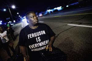 "Protester wears a black T-shirt with white writing that says ""Ferguson is Everywhere"""