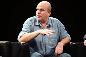 David Simon in light blue shirt against black background