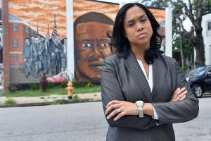 Marilyn Mosby in grey pinstriped suit with white shirt underneath against multi-colored mural of Freddie Gray and grey street