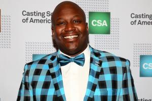 Titus Burgess in blue-and-black checkered tuxedo, blue bowtie and white shirt against gray background with green and blue logos