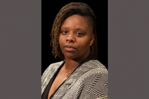 Black woman with brown dreadlocks and grey blazer and black shirt against black background